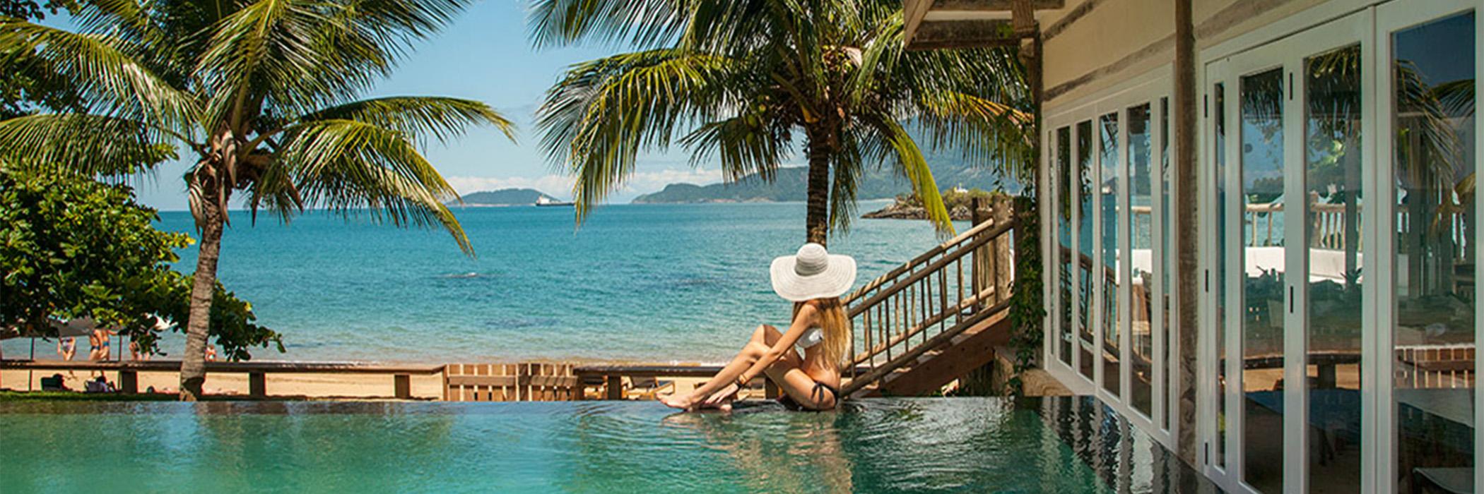 TW GUAIMBÊ EXCLUSIVE SUITES HOTEL = mulher sentada na piscina de chapeu